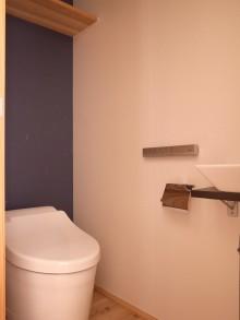 トイレ。便器背面は濃紺色の和紙クロス。