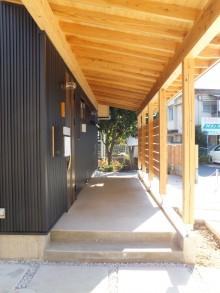 ガルバリウムの外壁と杉板で覆われた玄関アプローチ