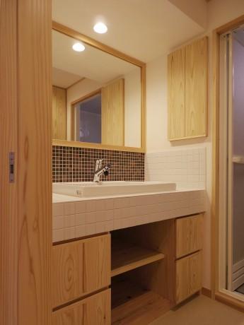 洗面室。モザイクタイルの天板と造作収納付の洗面台。