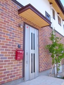 レンガの外壁と赤いポストが印象的な玄関まわり