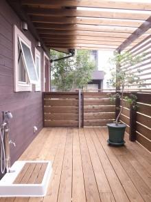 ウッドデッキから玄関方向を見る。木質の空間に緑が相性よくやわらかい印象を与えている。