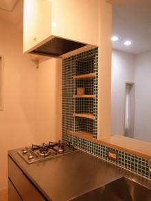 シンプルなオールステンレスのキッチンとブルーグリーンのモザイクタイルが印象的なキッチン。