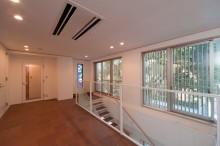 寺院向拝。階段を上がると、正面にステンドグラス、横には木格子ごしの緑が広がる。